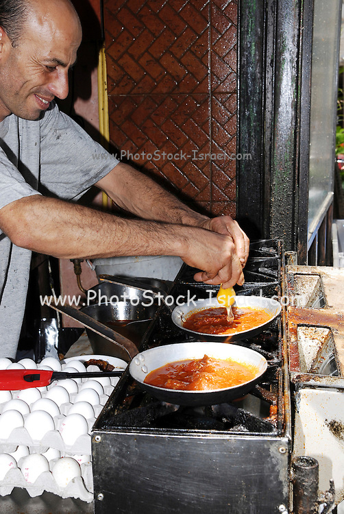 Israel, Jaffa, cooking Shakshuka a fried egg dish with tomatoes and onions a common Israeli dish, of North African origins
