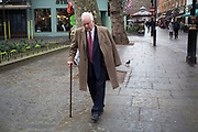 Elderly gentleman with a walking stick makes his way through the West End of London, UK.