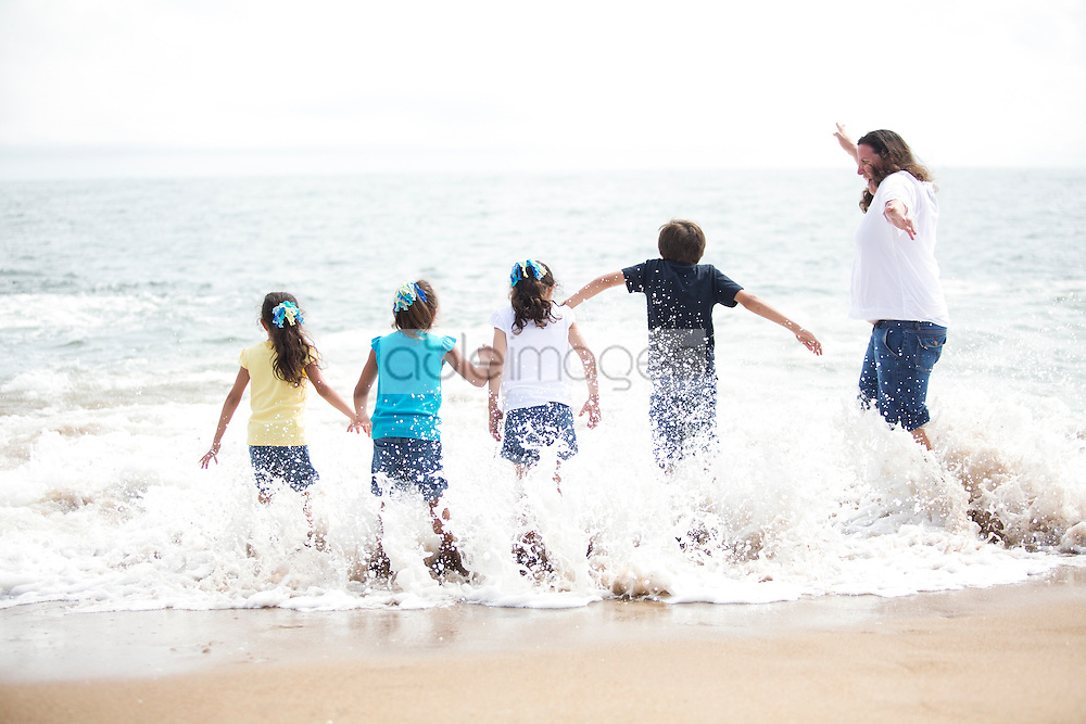 Back View of Family Running into the Sea