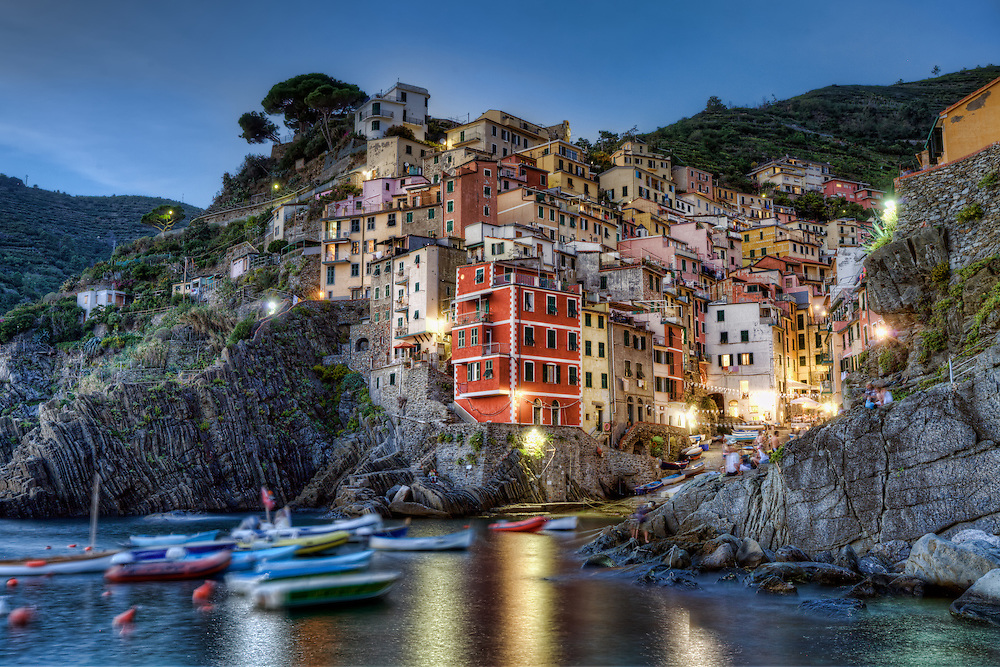 Riomaggiore is a village and comune in the province of La Spezia, situated in a small valley in the Liguria region of Italy. It is the first of the Cinque Terre one meets when travelling north from La Spezia. The village, dating from the early thirteenth century, is known for its historic character and its wine, produced by the town's vineyards. The village has shoreline on the Mediterranean's Gulf of Genoa, with a small beach and a wharf framed by the typical houses that have one or two-floor towers in order to use at best the place at disposal. Riomaggiore's main street is Via Colombo, where numerous restaurants, bars and shops can be found.