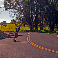 A young man skateboards down a lonely, winding road in the California Bay Area Foothills near Martinez.