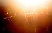 The sun rises as Grand Island Northwest flute players and the rest of the band rehearse their field show on Friday morning at Northwest High School. (Independent/Crystal LoGiudice).