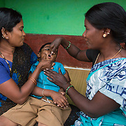 CAPTION: Accredited Social Health Activist (ASHA) Gurushanthi administers the polio vaccine to Mahendra while his mother holds him. Through the Chamkol programme's Early Years' Clubs, ASHAs like Gurushanthi will play more of a role in the lives of the youngest children with disabilities, like Mahendra, who has cerebral palsy. LOCATION: K K Hundi (village), Kasaba (hobli), Chamrajnagar (district), Karnataka (state), India. INDIVIDUAL(S) PHOTOGRAPHED: From left to right: Chiktayamma, Mahendra and Gurushanthi.