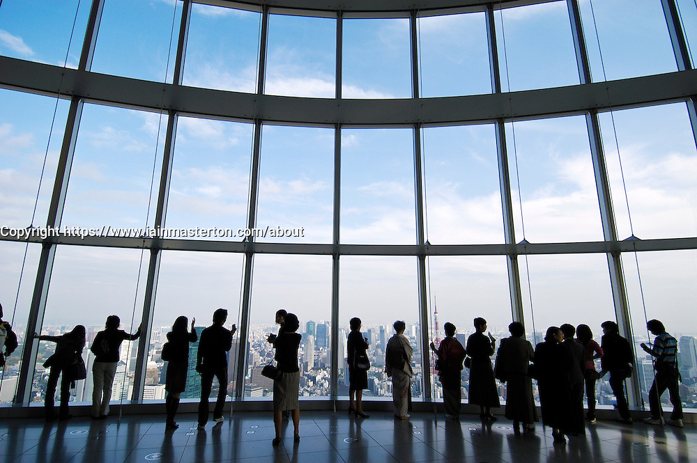 Visitors look out at Tokyo through large windows at  Tokyo City View in Mori Building Tokyo