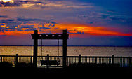 Sunset over bay with Silhouette of swing and fence