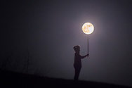 A girl wearing a hoodie stands silhouetted surrounded by darkness under a full moon appearing to balance the moon on a pole, as if holding a giant light.