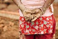 Ashmita Maharjan, 30, takes a brief break from carrying buckets of mud as workers rebuild a wall around a brick kiln outside of Kathmandu, Nepal.