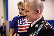 04 JULY 2012 - PHOENIX, AZ:  Sgt. JASON FRITZ, of the US Army, holds his son, LIAM FRITZ, 3, before Jason was naturalized as a US citizen Wednesday. Fritz, originally from Canada, served in the US Army for more than nine years as a Canadian citizen. About 250 people, from 62 countries, were naturalized as US citizens during the 24th Annual Fiesta of Independence naturization ceremony at South Mountain Community College in Phoenix Wednesday. The ceremony was presided over by the Honorable Roslyn O. Silver, Chief United States District Court Judge.   PHOTO BY JACK KURTZ