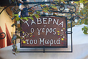 A Taverna sign in Greek in the Narrow Mnisikleous street, Plaka, Athens, Greece