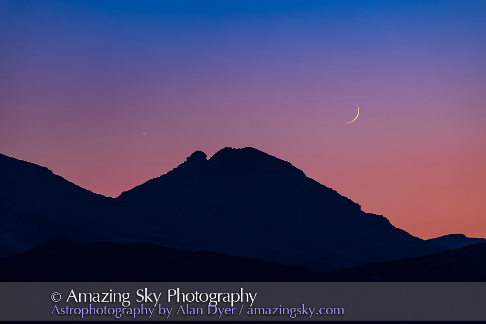 The conjunction of bright Venus with much dimmer Mars (to the left of Venus), with the waxing crescent Moon nearby, above the mountains of the Continental Divide at Waterton Lakes National Park, Alberta, on July 11, 2021. <br /> <br /> Mars was very dim and showed up on camera but was not visible to the naked eye or even readily in binoculars. <br /> <br /> This is a single shot with the 200mm Canon lens on the Canon EOS Ra, a red-sensitive camera that picks up more of the sunset reds in such twilight scenes.