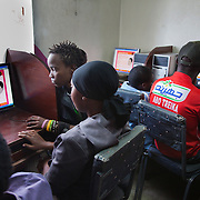 Youths using computers in a workshop run by Nairobits. The workshop involves information various life skills such as love and relationships and sexual education. Nairobits is a charity teaching kids from Nairobi's slums It and train them to get work in the IT sector.Every year 1mill young people graduate and leave school and only 1/3 have any hope of getting a job. Nairobits aim to train more than 500 young people / year from the slums, some with only basic formal education, how to set up their own business or get a job in the growing IT sector in Kenya.