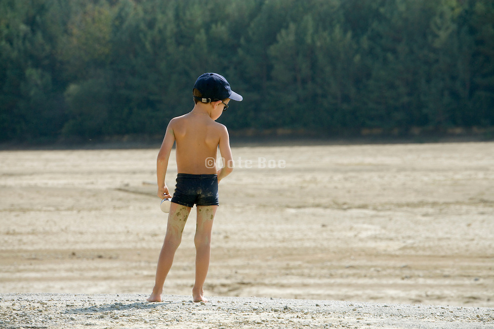 child playing at a dried up lake