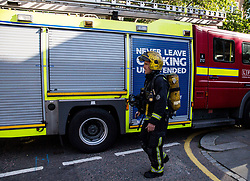 A firefighter close the scene after a fire engulfed the 24-storey Grenfell Tower in west London.