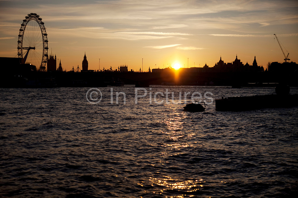 Setting sun over the River Thames. The sun replects of the water surface as a silhouette of the skyline points out the London Eye.