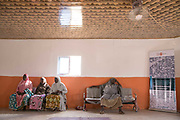 Aisha A, 28, at right, rests on a bench inside a communal building in an IDP camp along with other survivors of sexual violence by Boko Haram, Maiduguri, Nigeria, April 26, 2019. Aisha said she was abducted by seven BH fighters in Gwoza Local Government in 2014. After she was taken to a commander's house, she was raped by him and became the fourth wife. She stayed in his home for a year and eight months, but did not get pregnant. She got pregnant by an IDP man in the same camp with whom she married, and gave birth to a boy a day after this photo was taken.