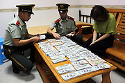 SHENZHEN, CHINA - JUNE 07: (CHINA OUT) <br /> <br /> Armed police officers pick off US dollars tied on a woman\'s legs on June 7, 2016 in Shenzhen, Guangdong Province of China. Armed police of Guangdong Frontier Defense Bureau arrested a woman tying 220,000 US dollars on her legs and a woman hiding over 3,000 memory cards at her private part when they were checked at the entry to Shenzhen on Tuesday.<br /> ©Exclusivepix Media