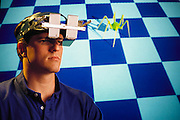 Virtual reality: Rich Holloway wears prototype headset which employs half-silvered mirrors to enable the user to view a projected image of a virtual environment (and thus exist in virtual reality) and also see in front of his nose. A virtual environment is one created by a computer. A person entering such an environment does so with the aid of such a headset, which displays virtual imagery. Tactile interaction with the environment may be made using a data glove, a Spandex garment wired with sensors, which relays movement of the hand & fingers to the virtual environment. Model Released (1990)