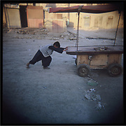 A boy pushes a cart very early in the morning in Kabul.