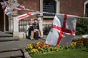 Elderly ladies sit in spring sunshine on England's national St George's Day the 23rd April outside the ancient Christian church of St. Botolph's without Bishopsgate in the City of London.