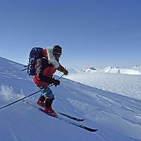 Tunabreen Glacier, Spitzbergen Island, Svalbard, Norway. An expedition skier descends wind blown snow on Nemtinov peak.