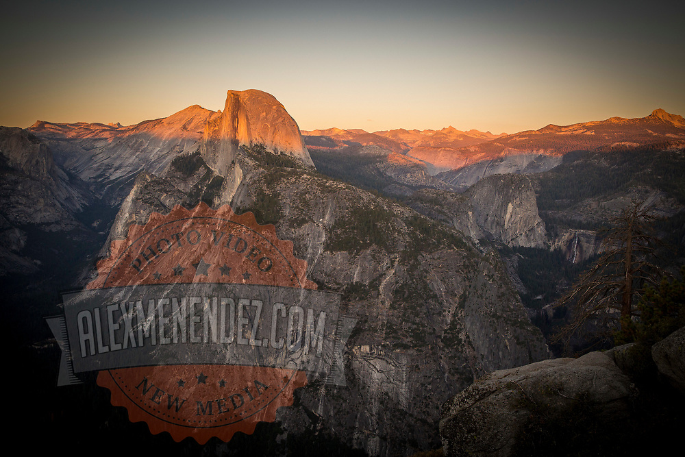 Half Dome is lit up at sunset in this view from Glacier Point inside Yosemite National Park on Sunday, September 22, 2019 in Yosemite, California. (Alex Menendez via AP)