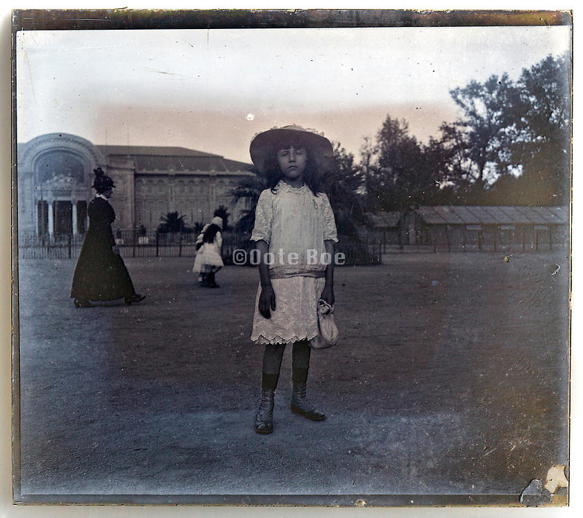 young girl with eyes closed in public park Paris France 1900s