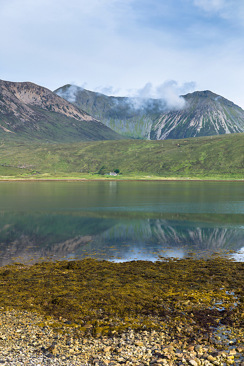 Small white solitary crofters cottage nestling below mountain range reflected in waters of the loch on Isle of Skye in the Highlands and Islands of Scotland