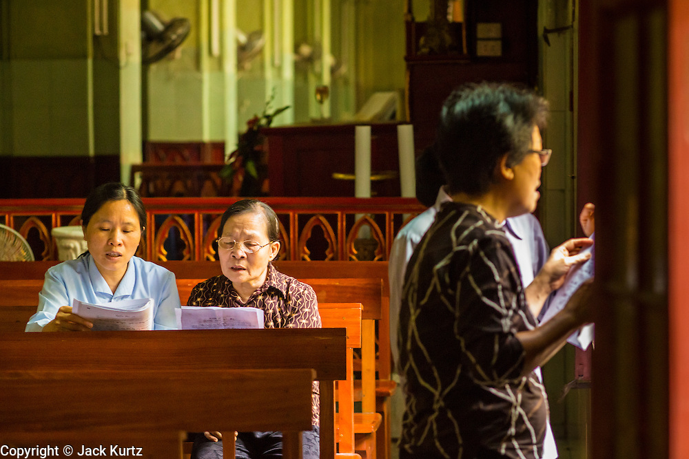 07 APRIL 2012 - HANOI, VIETNAM: Women pray before Easter in St. Joseph Catherdral in Hanoi, the capital of Vietnam. (In Vietnamese: Nhà th Ln Hà Ni, Nhà th Chính tòa Thánh Giuse) It is the seat of the Roman Catholic Archdiocese of Hanoi. The church was built in 1886 in the neo-gothic style.  Hanoi is one of the oldest cities in Southeast Asia. It was established in 1010 A.D.   PHOTO BY JACK KURTZ