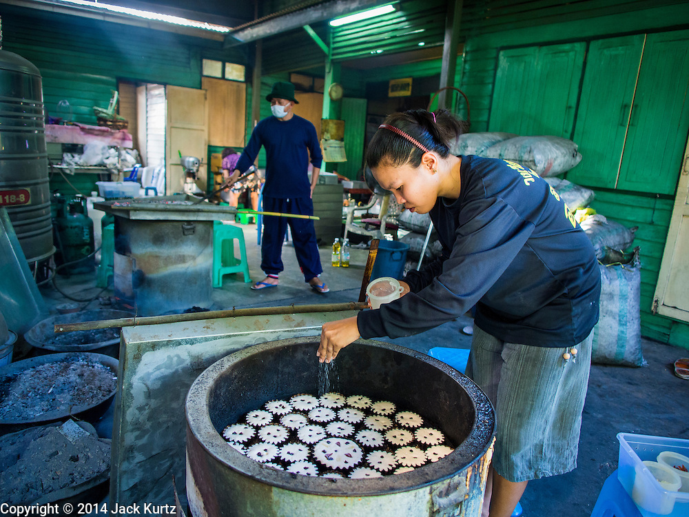 """28 OCTOBER 2014 - BANGKOK, THAILAND: A worker sprinkles sugar on top of cakes in a traditional oven at the Pajonglak Maneeprasit Bakery in Bangkok. The cakes are called """"Kanom Farang Kudeejeen"""" or """"Chinese Monk Candy."""" The tradition of baking the cakes, about the size of a cupcake or muffin, started in Siam (now Thailand) in the 17th century AD when Portuguese Catholic priests accompanied Portuguese soldiers who assisted the Siamese in their wars with Burma. Several hundred Siamese (Thai) Buddhists converted to Catholicism and started baking the cakes. When the Siamese Empire in Ayutthaya was sacked by the Burmese the Portuguese and Thai Catholics fled to Thonburi, in what is now Bangkok. The Portuguese established a Catholic church near the new Siamese capital. Now just three families bake the cakes, using a recipe that is 400 years old and contains eggs, wheat flour, sugar, water and raisins. The same family has been baking the cakes at the Pajonglak Maneeprasit Bakery, near Santa Cruz Church, for more than 245 years. There are still a large number of Thai Catholics living in the neighborhood around the church.   PHOTO BY JACK KURTZ"""