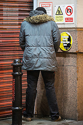 © Licensed to London News Pictures . 01/01/2016 . Manchester , UK . A man urinates in a corner . Revellers in Manchester on a New Year night out at the clubs around the city centre's Printworks venue . Photo credit : Joel Goodman/LNP