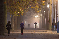 © Licensed to London News Pictures. 30/11/2020. London, UK. People exercise in a foggy St James's Park in central  London. Parts of the UK are experiencing heavy fog and low temperatures. Photo credit: George Cracknell Wright/LNP