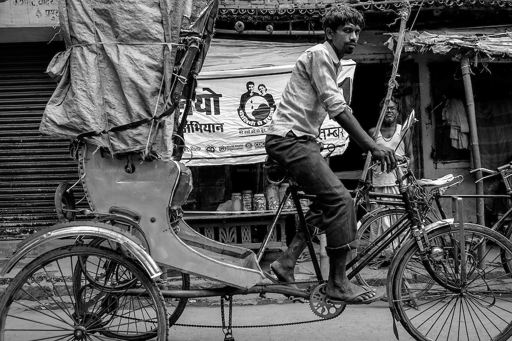 A bicycle rickshaw drives by a banner of the polio campaign at a muslim neighborhood of Patna, Bihar