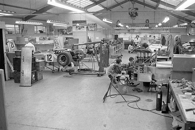McLaren race shop at Colnbrook, UK, circa May 1972. Mechanics Jim Stone and Vince Higgins and designer Gordon Coppuck confer behind M20 Can-Am car.