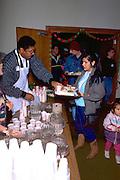 Volunteer serving Christmas dinner at church soup kitchen.  Minneapolis Minnesota USA