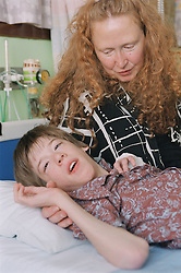 Mother comforting young boy with Cerebral Palsy who is lying on hospital bed on Children's ward in hospital; waiting for a Baclofen Implant pump operation,