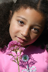 Close portrait of young girl holding a flower,