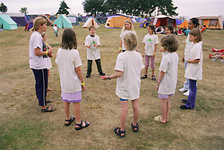 Group of children on environmental awareness camp standing in circle playing game,