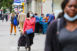 © Licensed to London News Pictures. 09/09/2020. London, UK. Shoppers wearing face coverings on Wood Green High Road, in the London Borough of Haringey as the number of COVID19 cases increases. As at Sunday, September 6, the government reported a three-month high in coronavirus cases in England, with 2,988 lab-confirmed cases reported on that day, the highest number of new cases since May. According to the figures published by the COVID-19 Symptom Study app, Newham, has most active cases among London boroughs, with 97 per 100,000 people.<br /> The London Borough of Haringey has 75.7 cases per 100,000 people. Britain could be facing a nationwide curfew as part of the efforts to avoid a second wave. Photo credit: Dinendra Haria/LNP