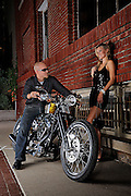 Brass Ball Bobber motorcycle in urban setting, with young biker in sunglasses flirting with hot chick in evening dress in front of brick building.  Model and product released.
