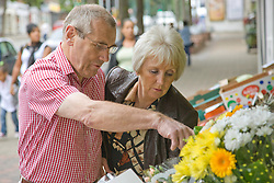 Older couple looking at flowers outside a green grocer shop,