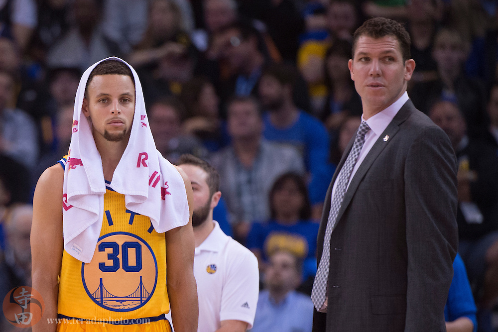 November 17, 2015; Oakland, CA, USA; Golden State Warriors guard Stephen Curry (30) and interim head coach Luke Walton (right) look on during the fourth quarter against the Toronto Raptors at Oracle Arena. The Warriors defeated the Raptors 115-110.