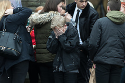 © Licensed to London News Pictures . 20/12/2017. Manchester, UK. A boy cries outside the church after the service . The funeral of 14-year-old Sam Berkley at Christ Church in Denton , East Manchester . Mourners wear red and white , the colours of Hattersley FC , for whom Berkley played . Amongst their number are pupils and friends from Audenshaw School . Berkley died after being hit by a grey BMW near junction 3 of the M67 in Hyde , East Manchester , on 1st December 2017 . Photo credit: Joel Goodman/LNP