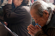 An old man prays at Togan-ji shrine in Sugamo, Tokyo, Japan. Monday February 4th 2008. Sugamo is affectionately known as the old lady Harajuku, in reference to the Mecca for youth fashions in the South of Tokyo, and is a popular place for Tokyo's increasingly aged population.