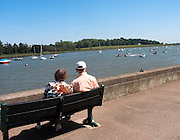 Elderly couple enjoying view over River Deben and boats, Woodbridge, Suffolk, England, UK