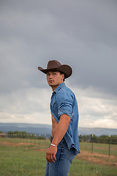 young good looking cowboy with open shirt outdoors on a ranch