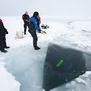 Katrin Iken monitors the progress of a fellow diver through a hole in the ice of the Arctic Ocean.