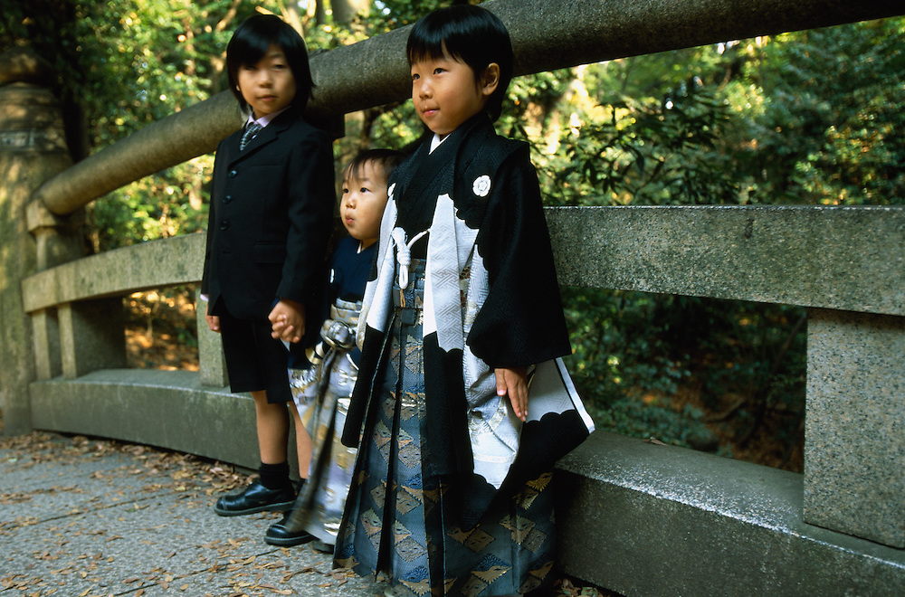 Two young boys and their older brother just before their shichi-go-san in the Meiji Jingu shrine, in Tokyo, Japan. During shichi-go-san, literally seven-five-three, parents dress their daughters aged three and seven and sons aged five in traditional costume and take them to a Shinto shrine to be blessed. Sometimes boys perform the ceremony at the age of three, though in bygone times they were not supposed to wear hakama trousers until they were older.