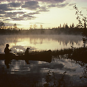 Man with a black lab in a canoe fishing on a small lake in northern Minnesota.