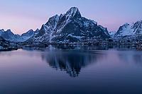 Winter twilight reflection of Osltind mountain peak in harbor at Reine, Moskenesøy, Lofoten Islands, Norway