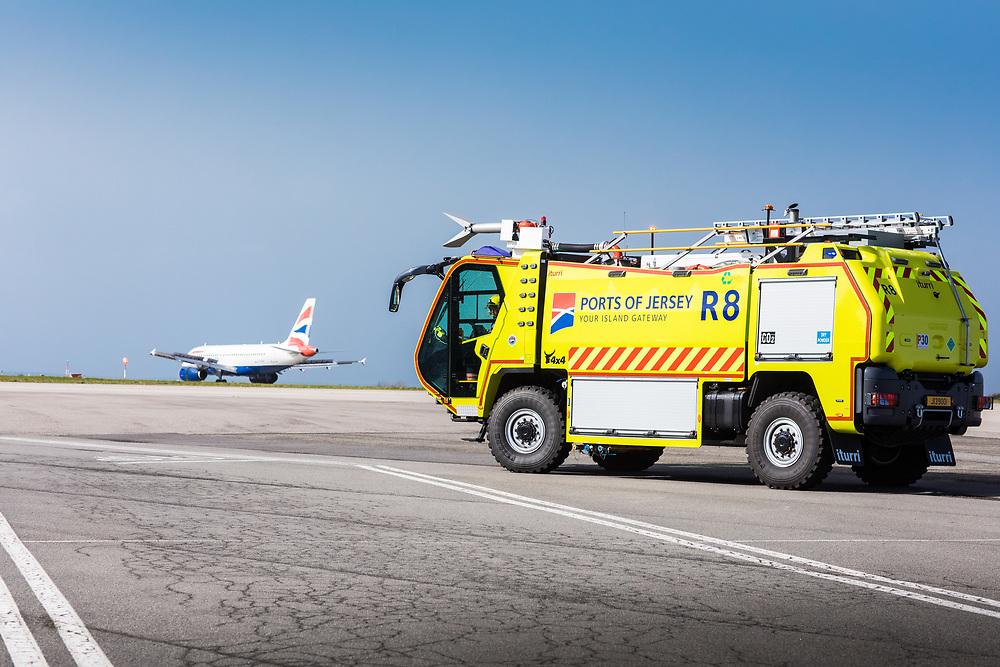 Firemen driving a fire engine around Jersey Airport with a British Airways aeroplane on the runway in Jersey, Channel Islands